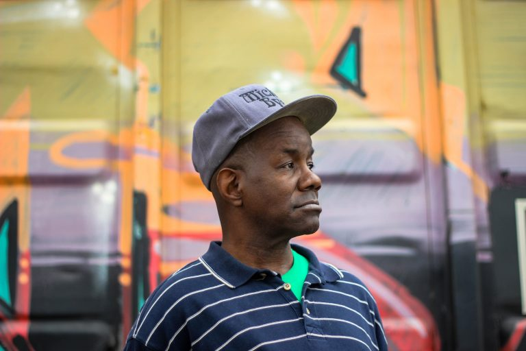 Photo of a man, with a baseball cap and polo on, looking into distance.