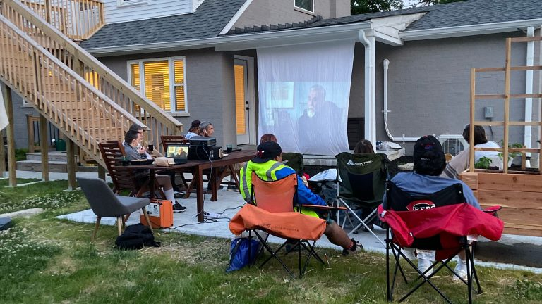 Photo of individuals watching movie outside.