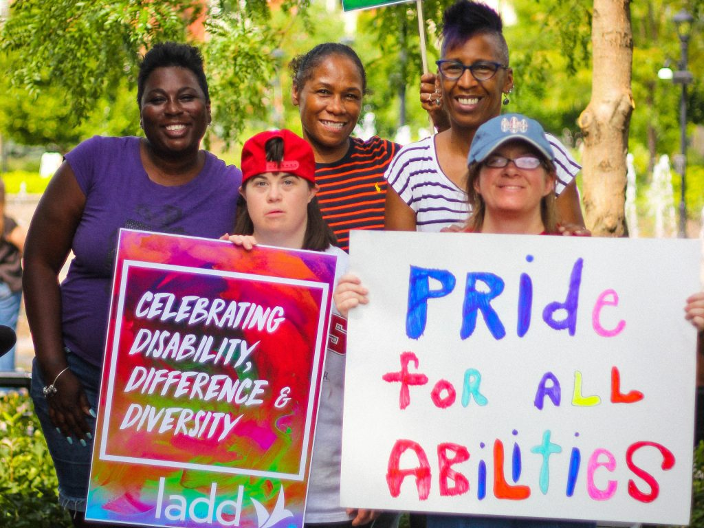 "Photo of group of women at the 2017 Pride March holding signs. One sign says, ""Pride for all abilities."" Another says, ""Celebrating disability, difference and diversity."""