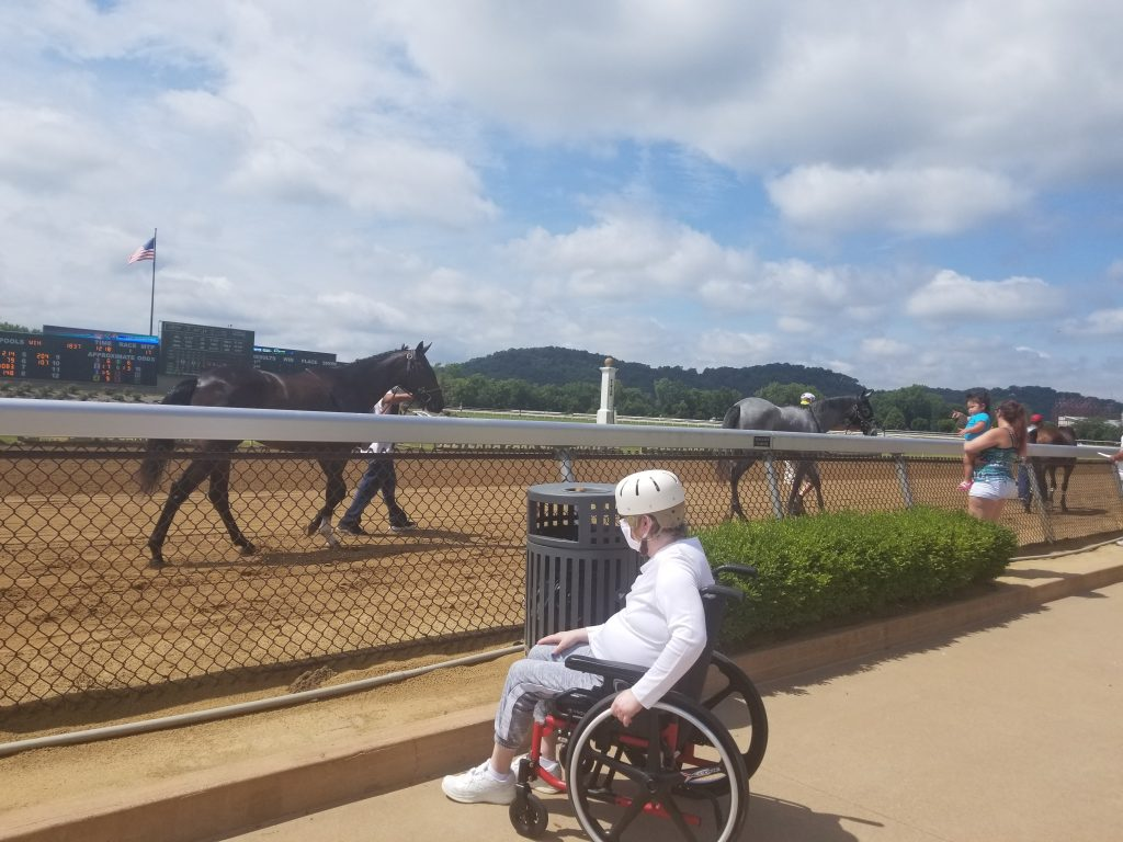 A person using a wheelchair is near a race track with horses.