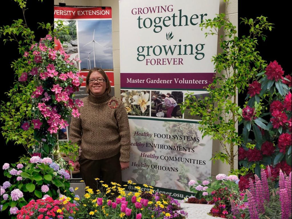 """Jenny Crowe stands in front of a sign that says """"Growing together, growing forever"""" with colorful flowers and plants surrounding her."""