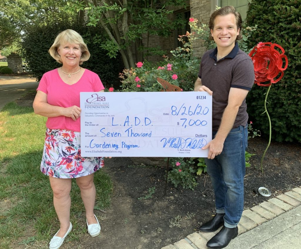 Photo of Ruth Klette and Jordan Klette-Cusher outside holding a large check.
