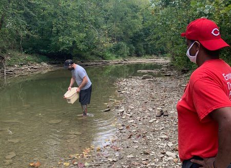 Photo of two men at a creek. One is in the creek looking for crawfish.