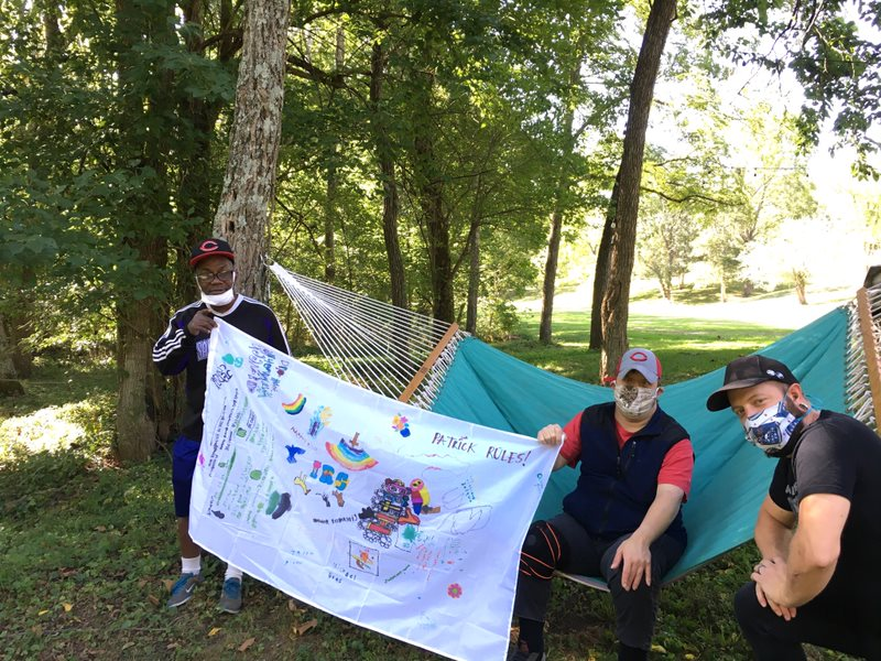 Photo of three men outside together with a hammock behind them. Two are holding a flag together.