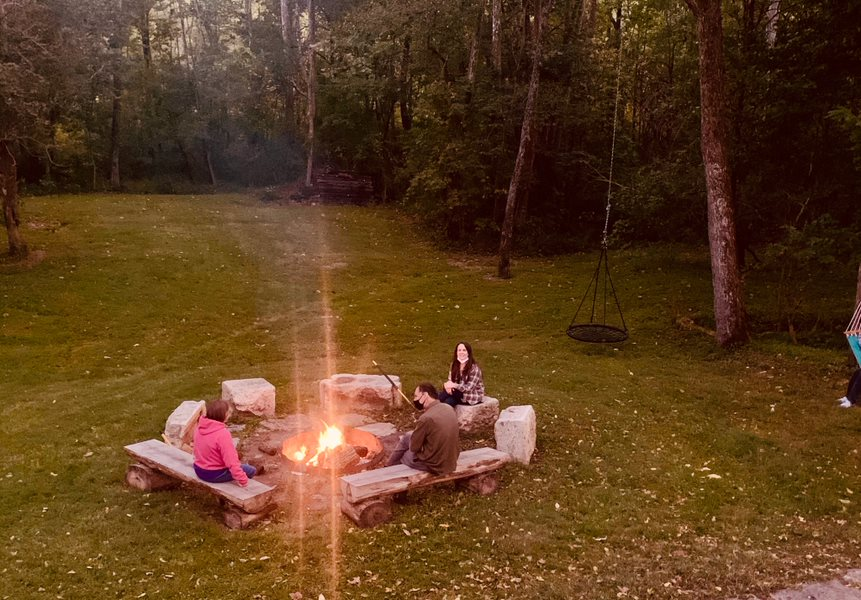 Photo of three people sitting, spaced out, around a fire outside.