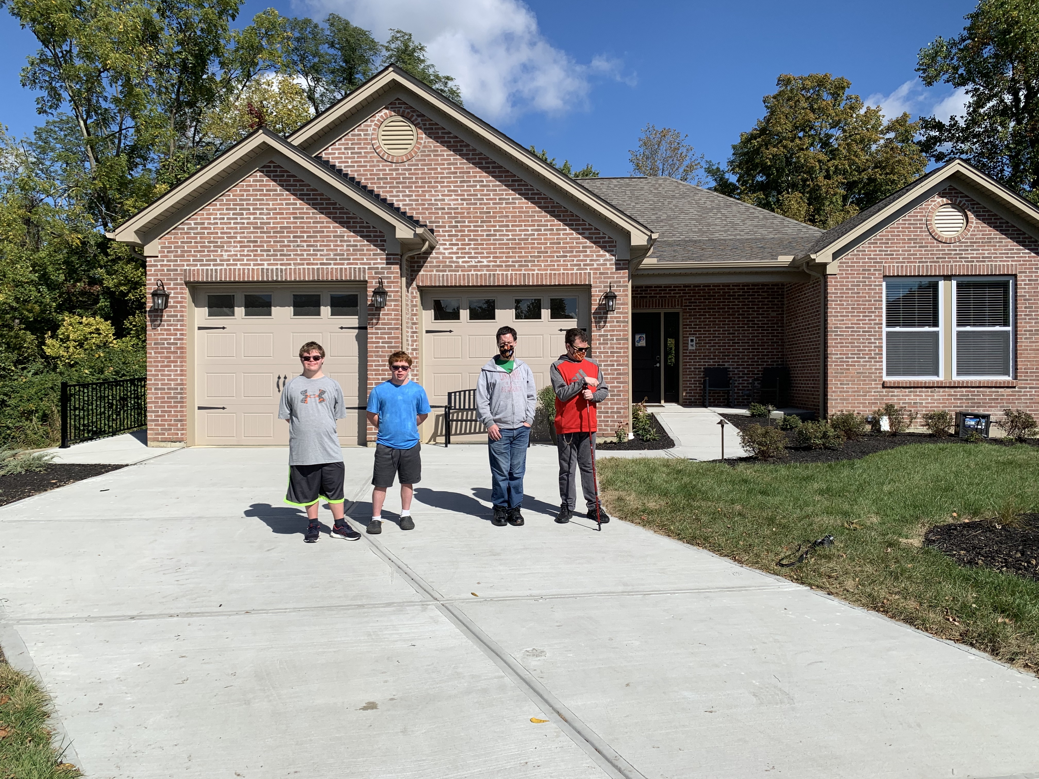 Four men, the residents of the Heidt Smart Living Home, stand in the driveway with the house behind them.