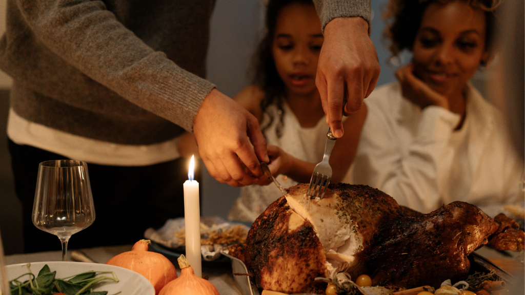 A cooked turkey is being cut into. A child and woman are in the background looking at the turkey.