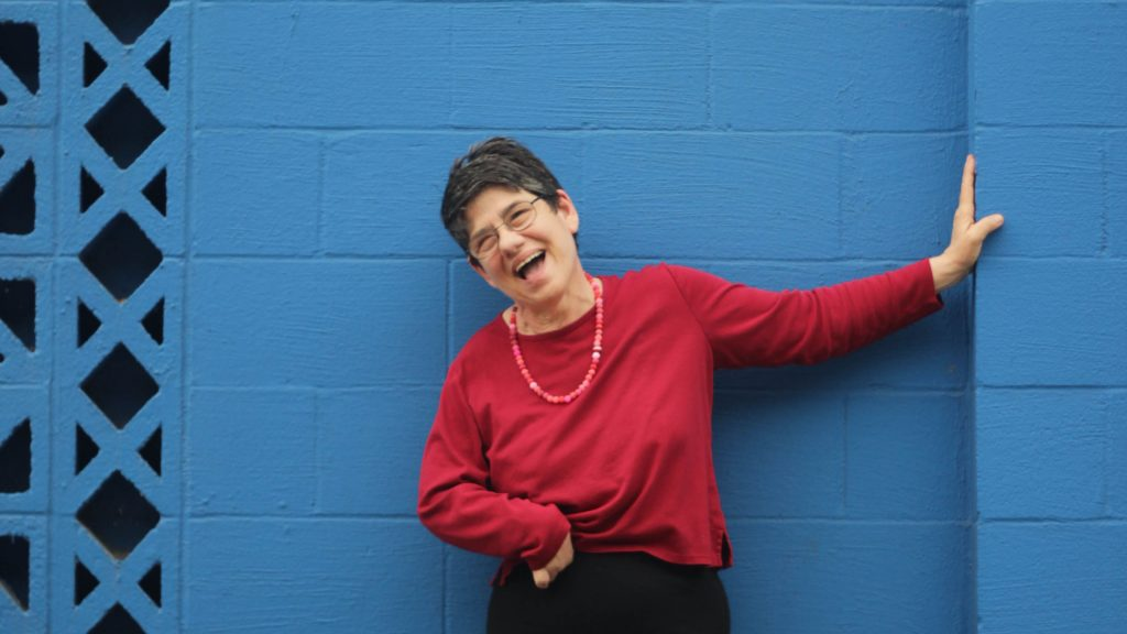 A woman with a red shirt on is smiling and learning up against a blue wall.